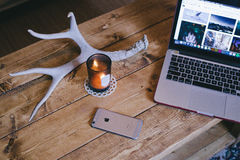 Macbook Pro Beside Brown Glass Candle Holder and Space Gray Iphone 6 on Brown Wooden Table Stock Images