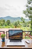 Macbook pro computer with flowers vase. SONGKHLA, THAILAND - August 11, 2018: Apple Macbook pro computer with flowers vase on wooden table, Mountain view stock image