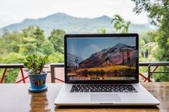 Macbook pro komputer z kwiat wazą obraz stock