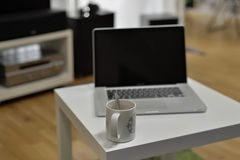 MacBook Pro lying on the table near o cup of coffee. From living room with sound and speakers devices Royalty Free Stock Image