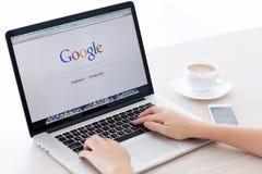 MacBook Pro näthinna och iPhone 5s med den Google hemsidan på scen