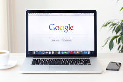 MacBook Pro Retina with Google home page on the screen stands on Stock Photo