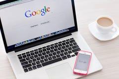 MacBook Pro-Retina und iPhone 5s mit Google-Homepage auf dem Sc Stockbilder