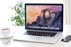 MacBook Pro siatkówka z OS X Yosemite jest na stole w daleko Obraz Royalty Free