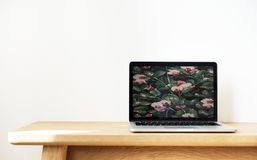 Macbook Pro on Top of Brown Desk Royalty Free Stock Image