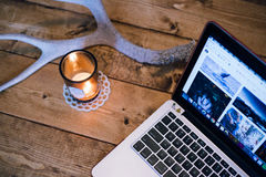 Macbook Pro Turned on Beside Brown Votive Candle Stock Photo
