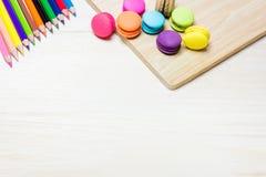 Maccherone disposto su una tavola di legno e di matite colorate multi fotografie stock