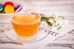 Maccherone, una tazza di tè e fiori sulla tavola fotografie stock