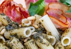 Maccheroni con il rigate del penne di pesto Con la cipolla ed il bacon, formaggio, basilico, pinoli, aglio fotografia stock