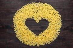 Maccheroni crudi - pasta Galetti In mezzo allo spazio vuoto sotto forma di un cuore Immagine Stock Libera da Diritti