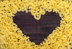 Maccheroni crudi - pasta Galetti In mezzo allo spazio vuoto sotto forma di un cuore Fotografia Stock Libera da Diritti