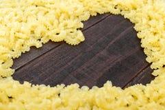 Maccheroni crudi - pasta Galetti In mezzo allo spazio vuoto sotto forma di un cuore Fotografia Stock