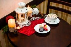 Maccheroni del dessert della Francia e cappuccino della tazza sulla tavola in caffè Immagine Stock