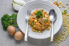Maccheroni fritti con l'uovo e carne di maiale e verdura in salsa al pomodoro i Fotografia Stock
