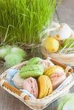 Maccheroni multicolori delle meringhe in un canestro di vimini delle uova di Pasqua su un fondo dell'erba per Pasqua Fotografie Stock