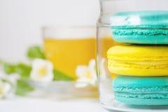 Maccheroni variopinti Macarons e tazza dolci di tè su fondo bianco con lo spazio della copia Fuoco selettivo Tempo di festa Fotografie Stock Libere da Diritti
