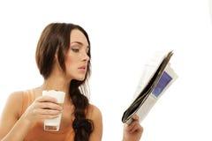 Macchi do latte da terra arrendada do jornal da leitura da mulher nova Fotografia de Stock
