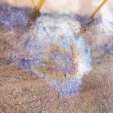 Macchia dell'arcobaleno dell'olio di motore sulla pavimentazione bagnata dell'asfalto Fotografia Stock
