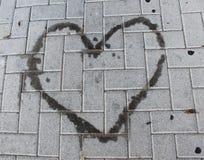 Macchia di olio in forma di cuore su un marciapiede Immagine Stock Libera da Diritti