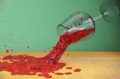 Macchia di vetro della sgocciolatura di moto di flusso della spruzzata del vino sulla tavola Fotografia Stock