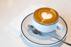 Macchiato coffee, with a heart decoration stock image