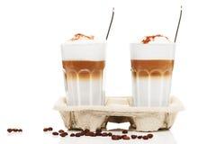 macchiato-de-dos-latte-con-el-polvo-del-chocolate-en-un-cupholder-con-los-granos-y-las-cucharas-de-café-en-el-fondo-blanco-29810658.jpg