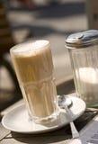 Macchiato van Latte en suikerautomaat op lijst Stock Afbeeldingen