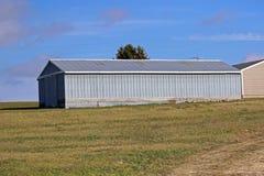 Macchina agricola del metallo sparsa sotto cielo blu Fotografia Stock