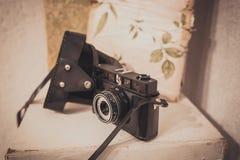 Macchina da presa d'annata con il caso di cuoio su fondo bianco Fotografia Stock