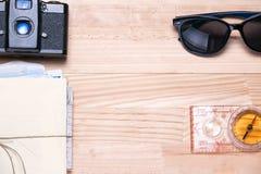 Macchina da presa d'annata, mazzo di lettere, occhiali da sole e una bussola Immagini Stock