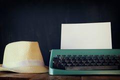 Macchina da scrivere d'annata con la pagina in bianco accanto al cappello della fedora Fotografia Stock