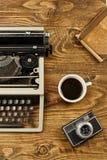 Macchina da scrivere d'annata, tazza di caffè, macchina fotografica e un taccuino su woode Fotografie Stock Libere da Diritti