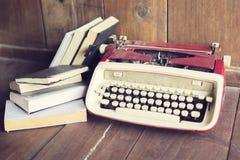 Macchina da scrivere di vecchio stile con i libri sul pavimento di legno fotografia stock