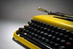 Macchina da scrivere gialla d'annata in riflettore evocativo Immagine Stock