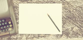 Macchina da scrivere, matita e carta sul vecchio scrittorio di legno misero Derisione su Effetto opaco d'annata fotografie stock