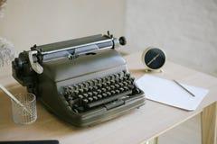 Macchina da scrivere da tavolino e retro inventario del lavoro: orologio, matita, carta fotografie stock