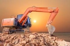 Macchina del caricatore di escavatore con il fondo di tramonto fotografie stock
