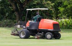 Macchina del falciatore di guida del giardiniere del lavoro dell'uomo nel campo da golf Fotografie Stock