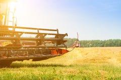Macchina della mietitrice nel campo nei raggi del sole Agricoltura e f Fotografia Stock