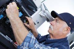 Macchina di fotocopia di apertura dell'uomo del tecnico in ufficio Fotografia Stock