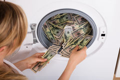 Macchina di Person Inserting Money In Washing Fotografie Stock