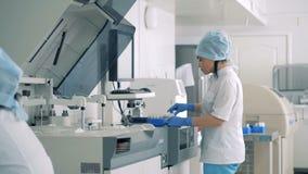 Macchina di prova del carico dei tecnici di laboratorio con i campioni di sangue video d archivio