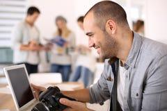 Macchina fotografica allegra della tenuta del reporter che lavora al computer portatile fotografia stock