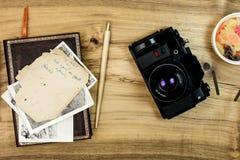 Macchina fotografica analogica con le vecchie foto su vecchio legno Immagine Stock Libera da Diritti