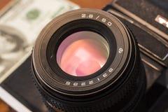 Macchina fotografica antica con molti dollari Fotografia Stock