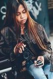 Macchina fotografica attraente della tenuta della giovane donna ed esposimetro in sue mani in uno stile alla moda Fotografia Stock
