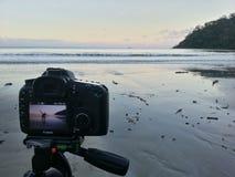 Macchina fotografica che mostra persona su una spiaggia vuota al tramonto Fotografia Stock
