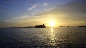 Macchina fotografica che si avvicina ad una nave da carico al tramonto archivi video