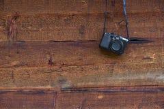 Macchina fotografica compatta digitale d'annata della foto che appende su una parete di legno Immagini Stock