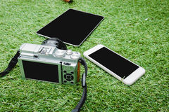 Macchina fotografica, compressa e smartphone su un fondo dell'erba Fotografia Stock Libera da Diritti